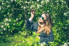 La jeune femme de sourire heureuse dans les lunettes de soleil et une veste tricotée appréciant le ressort fleurit dans le jardin Images stock