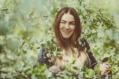 La jeune femme de sourire heureuse dans une veste tricotée appréciant le ressort fleurit dans le jardin Image libre de droits