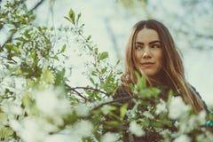 La jeune femme de sourire heureuse dans une veste tricotée appréciant le ressort fleurit dans le jardin Photos libres de droits