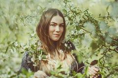 La jeune femme de sourire heureuse dans une veste tricotée appréciant le ressort fleurit dans le jardin Image stock