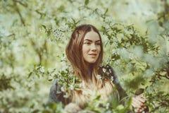 La jeune femme de sourire heureuse dans une veste tricotée appréciant le ressort fleurit dans le jardin Photographie stock libre de droits