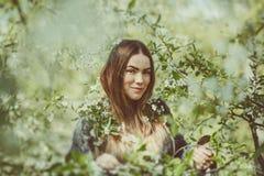La jeune femme de sourire heureuse dans une veste tricotée appréciant le ressort fleurit dans le jardin Photos stock