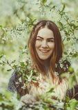 La jeune femme de sourire heureuse dans une veste tricotée appréciant le ressort fleurit dans le jardin Images stock