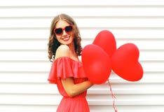 La jeune femme de sourire heureuse portant la robe rouge et les lunettes de soleil avec le coeur de ballons à air forment au-dess Images libres de droits