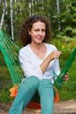 La jeune femme de sourire s'assied dans l'hamac avec la fleur jaune qu'elle se tient Photo libre de droits