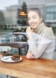 La jeune femme de sourire s'assied en café Photos libres de droits