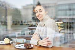 La jeune femme de sourire s'assied en café Photographie stock