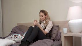 La jeune femme de sourire surfe le smartphone d'utilisations d'Internet après jour difficile de travail Image libre de droits