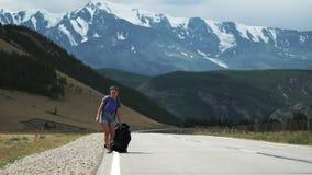 La jeune femme de touristes d'auto-stoppeur traîne le sac à dos et a jeté un sac à dos sur des fps d'une route 50 de montagne banque de vidéos
