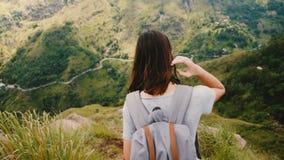 La jeune femme de touristes de vue arrière avec le sac à dos ramène le chemin extrêmement raide de montagne, vue épique dans le m banque de vidéos