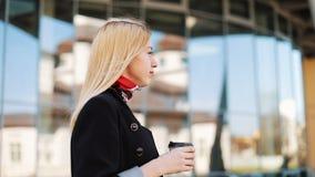 La jeune femme de transsexuel marche avec une tasse de café le long du mur de miroir dehors banque de vidéos
