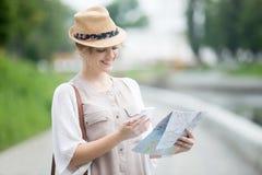 La jeune femme de voyageur tenant la carte et le téléphone pendant à l'étranger se déclenchent images stock