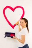 La jeune femme dessine le coeur rouge de peinture Photo libre de droits