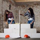 La jeune femme deux aux cheveux longs a construit un nouveau mur Images stock