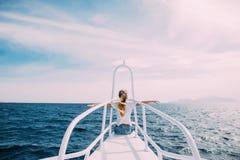 La jeune femme devant le nez du yacht blanc avec les mains augmentées apprécient le vent et la mer Vocation d'été Images stock