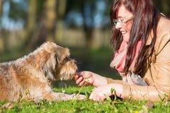 La jeune femme donne à son chien un festin photographie stock