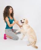 La jeune femme donne un morceau de pomme à son chien image stock