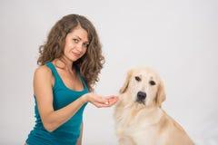 La jeune femme donne un morceau de viande ? son chien photo stock
