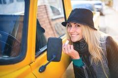 La jeune femme douce applique le rouge à lèvres rouge regardant le miroir de voiture Images stock