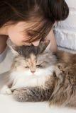 La jeune femme embrasse le dessus de sa tête du ` s de chat Image libre de droits