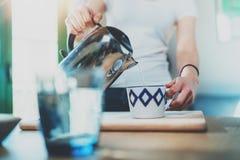 La jeune femme employant la bouilloire pour font le thé ou le café noir sur la cuisine au fond d'intérieur de pièce Les mains du  Images libres de droits