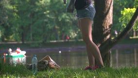 La jeune femme en parc se lève et marche loin banque de vidéos
