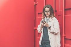 La jeune femme en verres se tient dehors sur le fond rouge de mur en métal, regardant l'écran du téléphone, smartphone d'utilisat Photos libres de droits