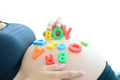La jeune femme enceinte avec la lettre bloque le garçon d'orthographe sur son ventre enceinte Photo libre de droits