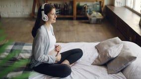 La jeune femme enceinte gaie frotte son ventre et écoute la musique appréciant les écouteurs de port de belle chanson clips vidéos