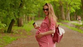 La jeune femme enceinte marche par le parc et les sourires à la caméra Tir moyen banque de vidéos