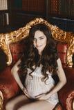 La jeune femme enceinte sensuelle et belle de brune avec le maquillage tendre dans les sous-vêtements blancs de dentelle, s'assie photo libre de droits