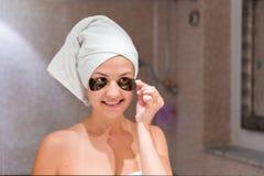 La jeune femme enl?ve des corrections de sous-oeil regardant dans le miroir ? la maison dans la salle de bains Soins de la peau d images stock