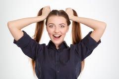 La jeune femme enthousiaste drôle avec deux queues de cheval holded à la main Photo stock