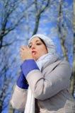 La jeune femme essaye de chauffer ses mains gelées en parc du d'hiver Images stock