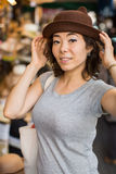 La jeune femme essaye un chapeau au magasin Photo stock