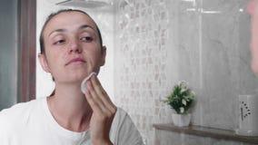 La jeune femme essuie son visage par la protection de coton avec la lotion de nettoyage dans la salle de bains clips vidéos