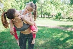 La jeune femme est extérieur debout en parc et participation sa fille sur elle de retour Elle la tient sur ses jambes et regard image libre de droits