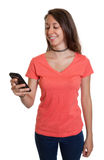 La jeune femme est heureuse au sujet d'un message au téléphone photo libre de droits