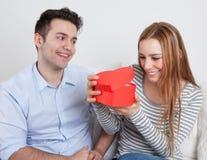 La jeune femme est heureuse au sujet du cadeau de son ami Photographie stock