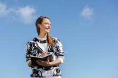La jeune femme est pensante et prenante des notes Photo stock