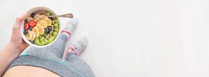 La jeune femme est reposante et mangeante une farine d'avoine saine après une séance d'entraînement photos libres de droits