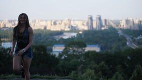 La jeune femme est tendrement engagée dans la forme physique dans des chaussures de sauts de kangoo sur le fond de la ville 4K MO banque de vidéos