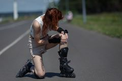 La jeune femme est tombée sur la route et a meurtri son genou pendant le patinage photos stock