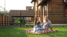 La jeune femme et l'homme heureux s'asseyent avec peu de garçon sur la pelouse clips vidéos