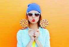 La jeune femme et la lucette de portrait de mode a l'amusement au-dessus de l'orange colorée Photographie stock