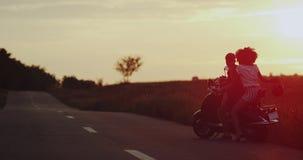 La jeune femme et les hommes, sont prêts pour un tour sur leur rétro moto, ils sont prêts pour aller porter leur casque banque de vidéos