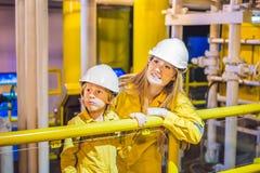 La jeune femme et un petit garçon sont tous deux dans un uniforme jaune, les verres, et le casque de travail dans un milieu indus photos stock
