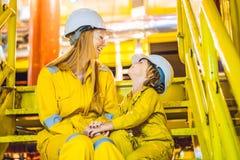 La jeune femme et un petit gar?on sont tous deux dans un uniforme jaune, les verres, et le casque de travail dans un milieu indus photo libre de droits