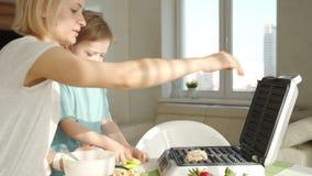 La jeune femme faisant cuire des gaufres dans la cuisine et le gar?on mignon l'aide Famaly faisant cuire le petit d?jeuner t?t le banque de vidéos