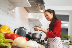 La jeune femme faisant cuire la nourriture romantique de dîner à la maison est mauvaise Photos stock